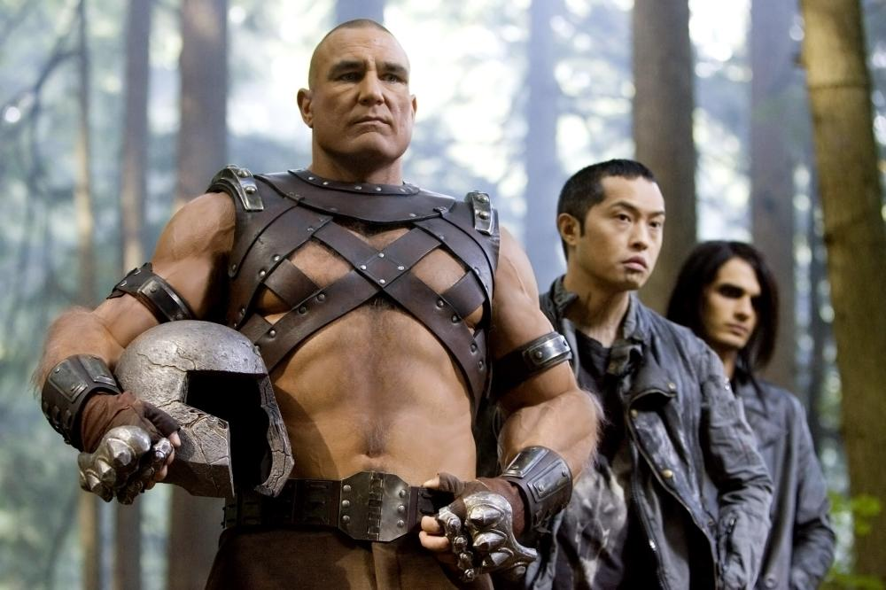 Vinnie Jones as Juggernaut, wearing a leather strapped shirt, and holding his helmet under his right arm