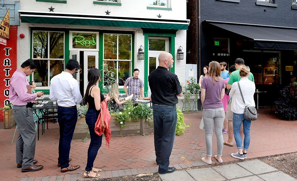 line of people outside a restaurant waiting for table