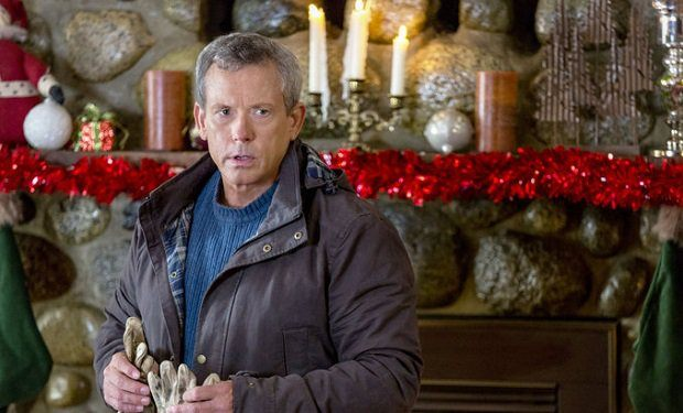 Williw Aames as Vernon in front of a mantle decorated for Christmas