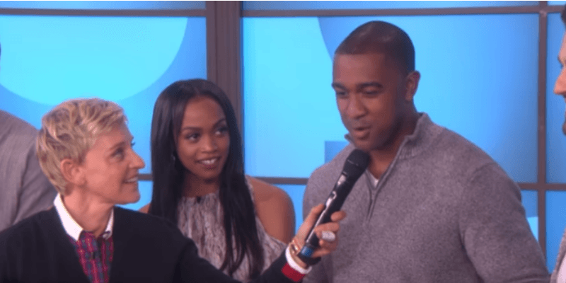Ellen is holding a microphone to Will G's face and Rachel Lindsay is next to him looking at him.