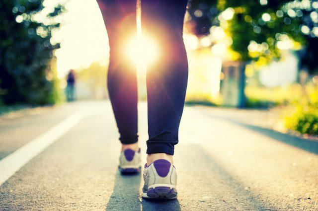 A woman with running shoes walks along a park path.