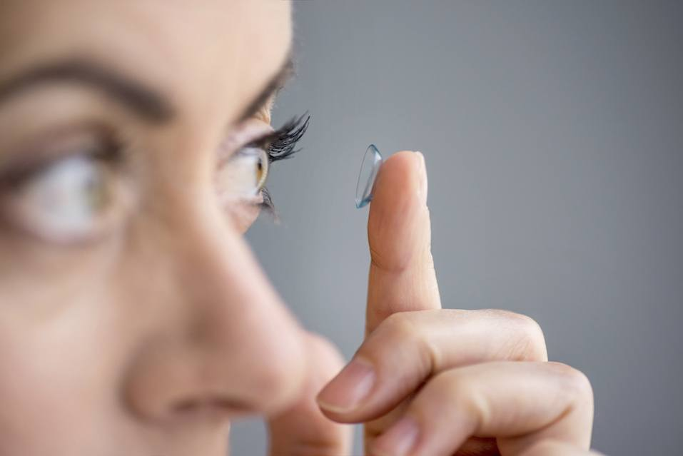 Woman putting contact lenses in her eyes