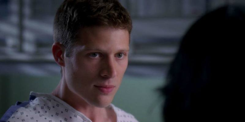 This is a closeup of Zach Gilford in a hospital gown looking at someone.