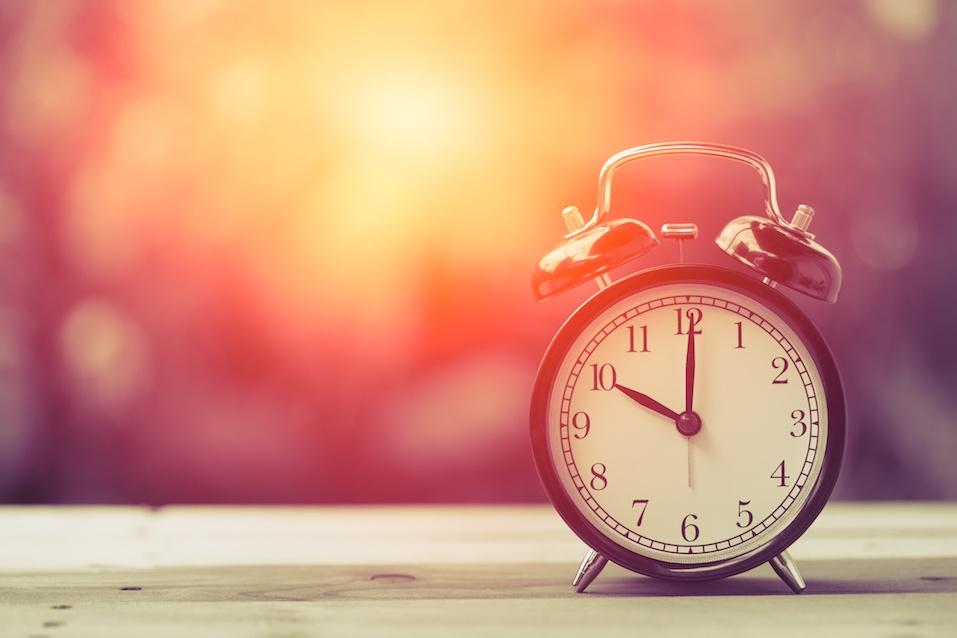 10 o'clock Clock Vintage on Wood Table with Sun Light