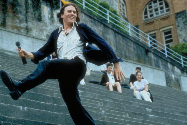 Heath Ledger, kicking his leg out in the bleachers of a football stadium and laughing