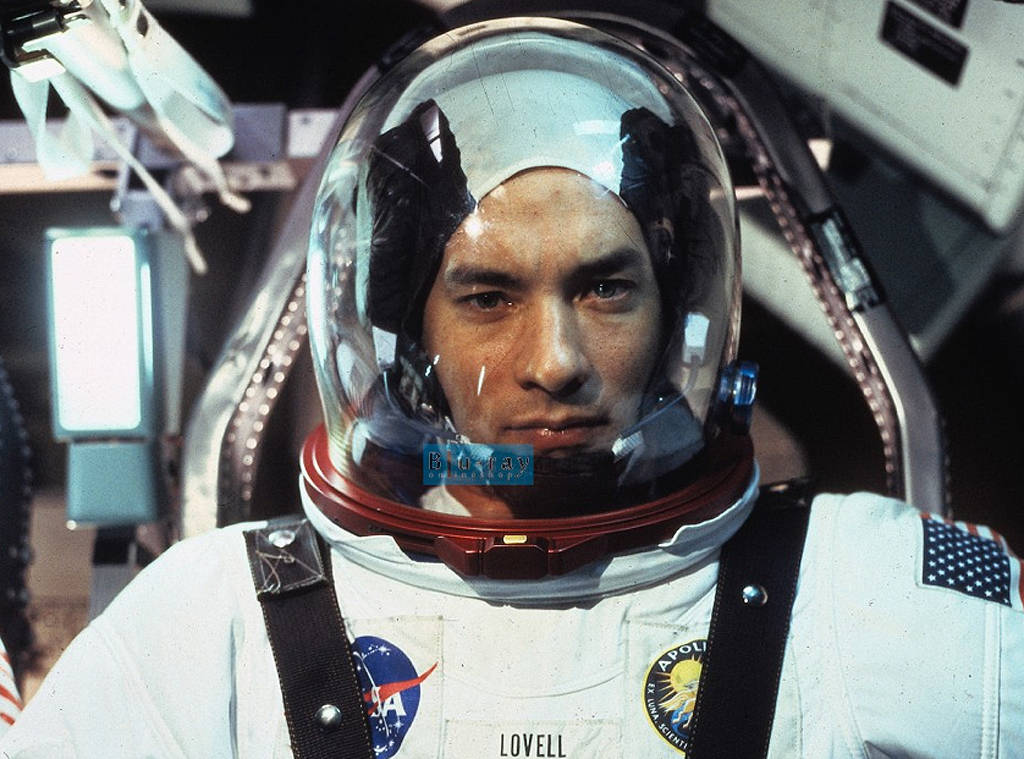 Tom Hanks wears a space suit and helmet while sitting in spacecraft in Apollo 13