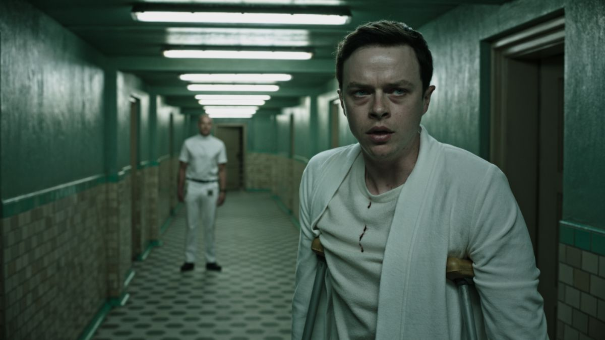 Dane DeHaan stands on crutches in a hallway in A Cure for Wellness