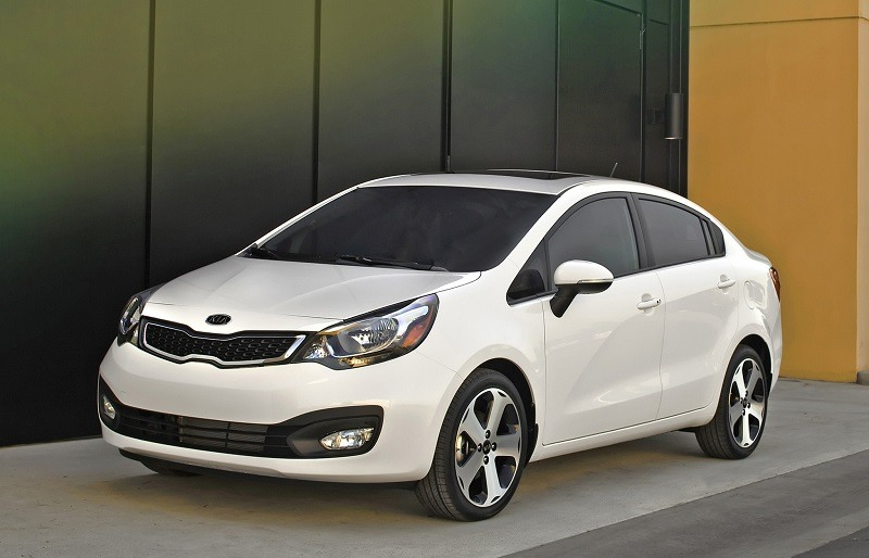 Front three quarter view of 2013 Kia Rio sedan in white