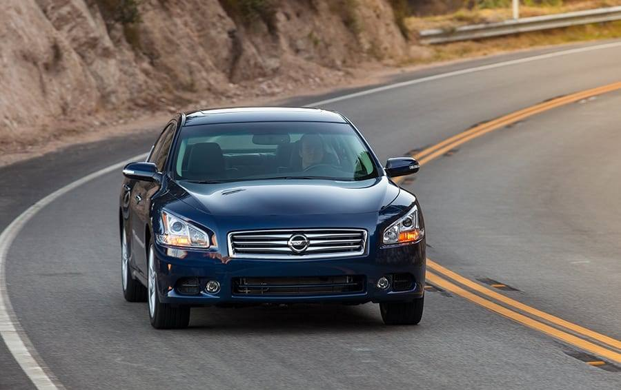 Front view of blue 2014 Nissan Maxima on a winding road