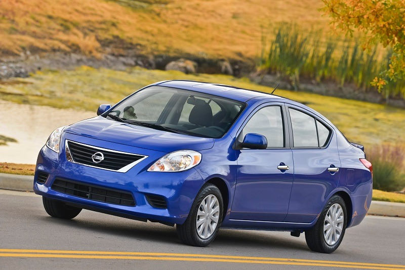 VIew of 2014 Nissan Versa in blue on a country road