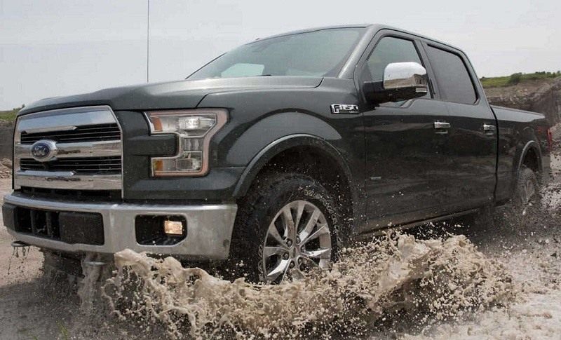 Action shot of dark gray 2017 Ford F-150 moving through a muddy puddle
