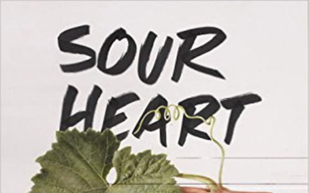 A bunch of grapes rest on a white table on the cover of Sour Heart