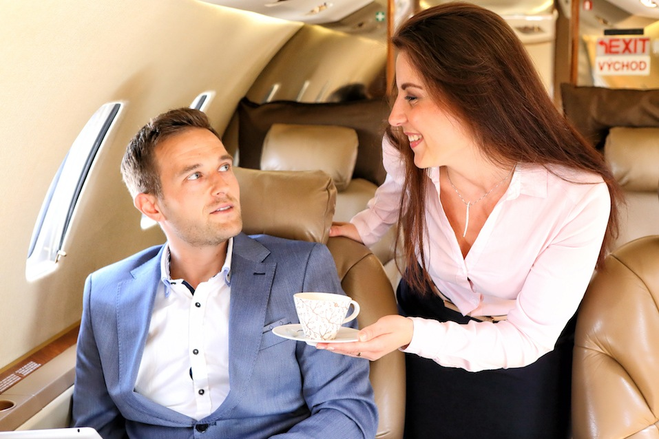 Executive jet stewardess bringing the cup of coffee to the passenger
