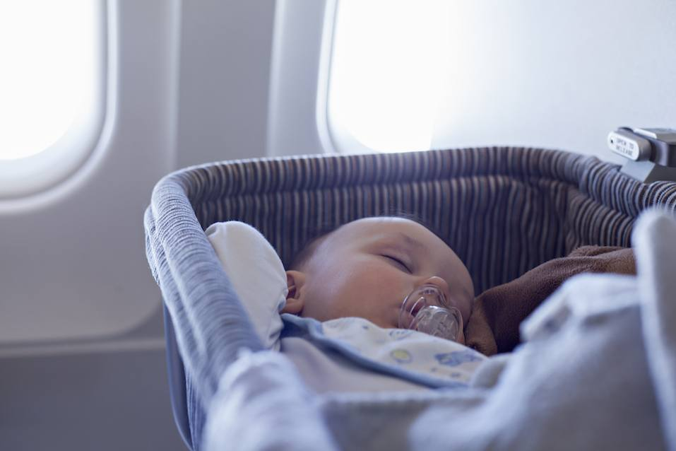Adorable Baby Boy Sleeping In Special Bassinet On Airplane