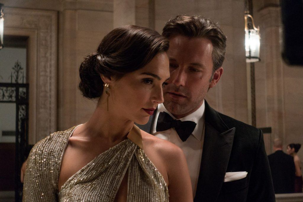Gal Gadot in a gown standing in front of Ben Affleck in a tuxedo in Batman v Superman: Dawn of Justice