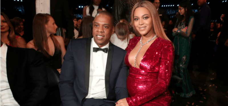 Beyonce is wearing a red dress next to Jay Z in a tux.