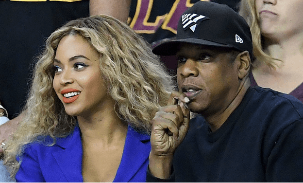 Beyonce is in a blue suit and Jay are watching a NBA Finals game.