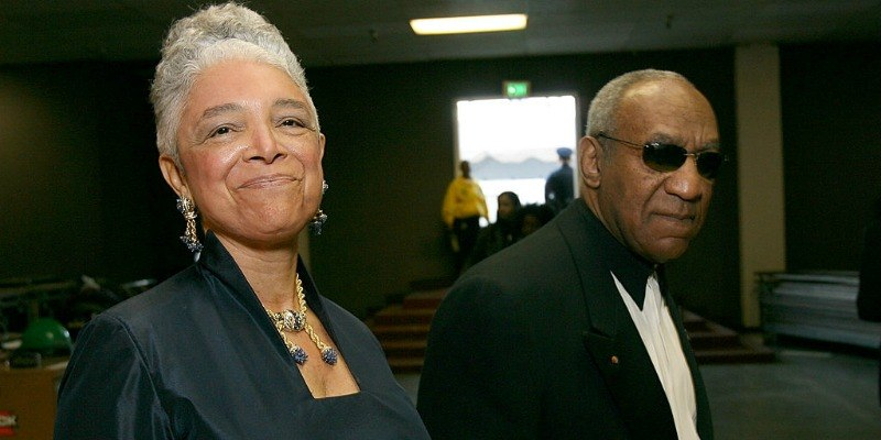 Bill and Camille Cosby are walking next to each other.