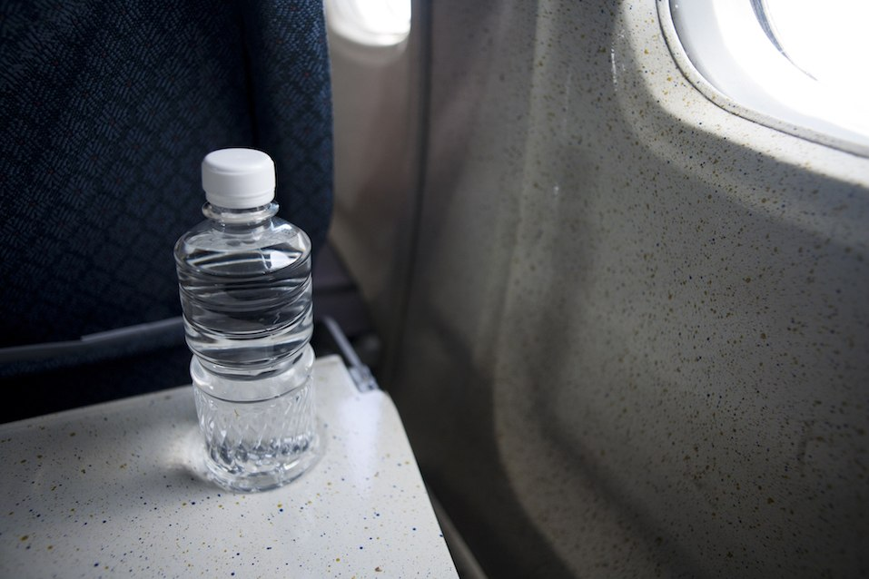 unopened bottle of water on a tray table in airplane