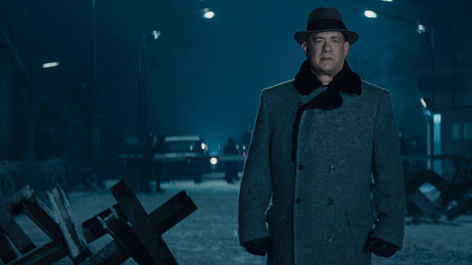 Tom Hanks stands in an empty street wearing a coat and a fedora in Bridge of Spies