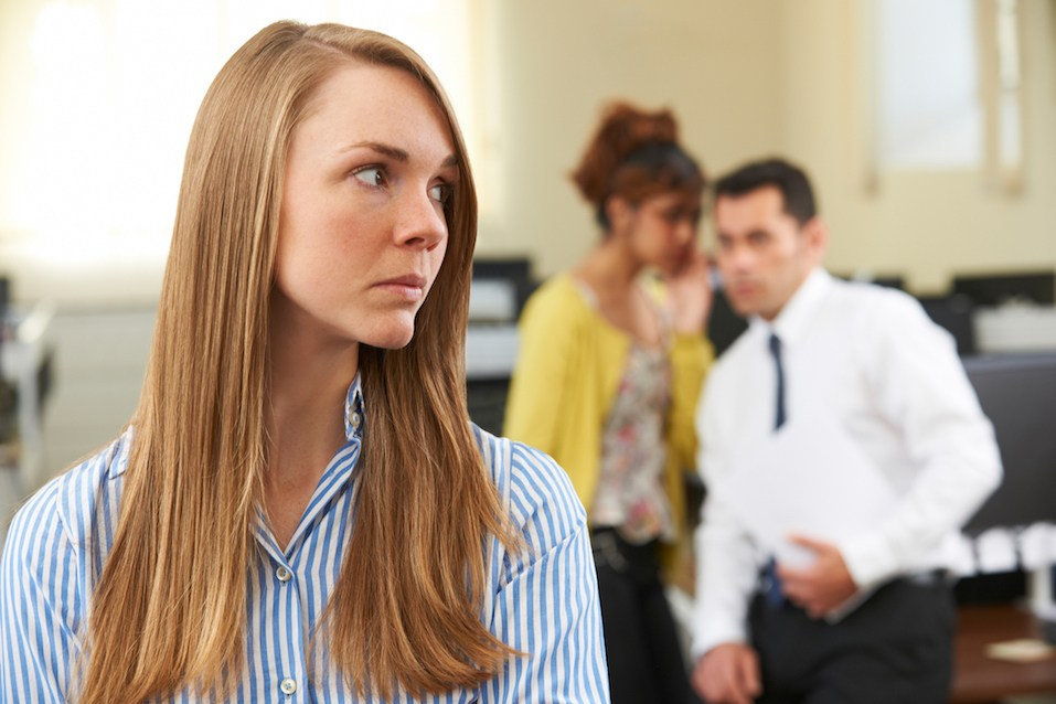 colleagues gossiping about a female co-worker