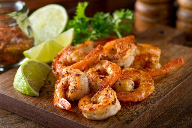 Shrimp and sliced limes on a wooden board.