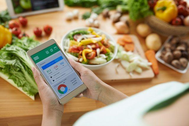 A woman uses a calorie counter application on smartphone.