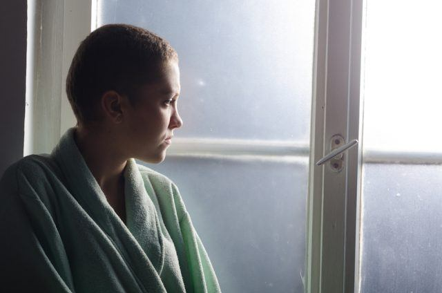 Young depressed cancer patient standing in front of hospital window.