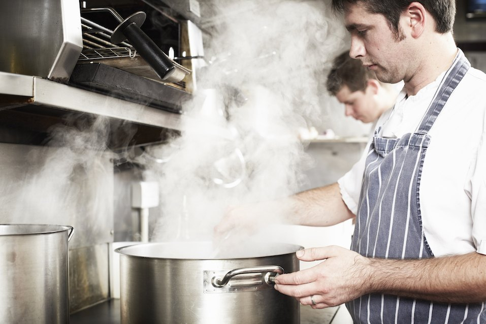 Chef boiling water in kitchen