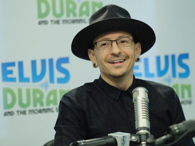 Chester Bennington smiling and wearing a black fedora.