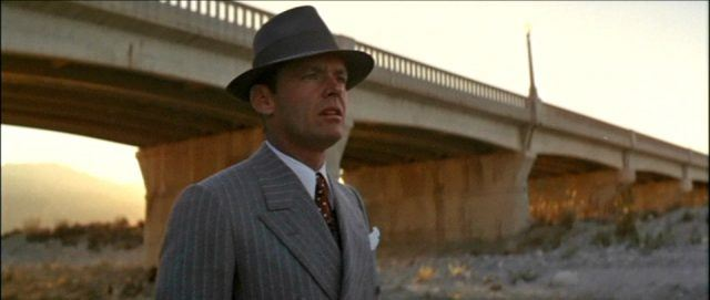Jack Nicholas, standing under a bridge, wearing a fedora, and looking off into the distance