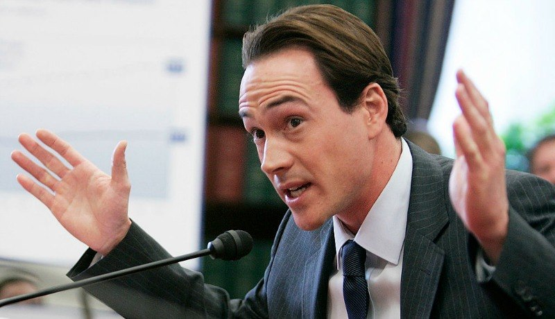 Chris Klein is talking into a microphone with two hands up in the air.
