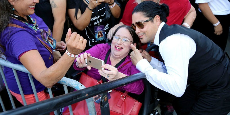 Chris Perez is bending down posing with a fan for a selfie.