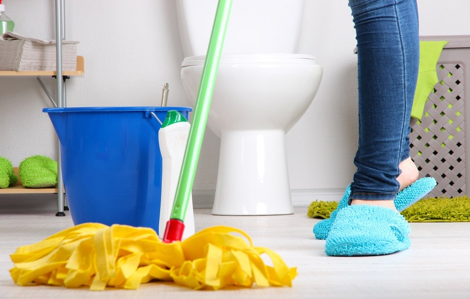 person in slippers mopping bathroom floor
