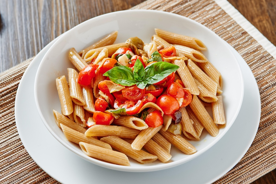 Close-up of pasta penne with cherry tomatoes on white plate surrounded by ingredients - vegan food