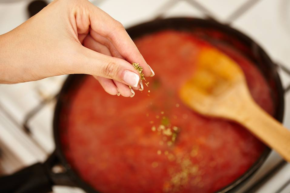 Closeup cook's hand sprinkling chopped parsley and basil in the tomato sauce pan on the stove