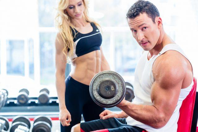 Couple in fitness gym lifting weights.