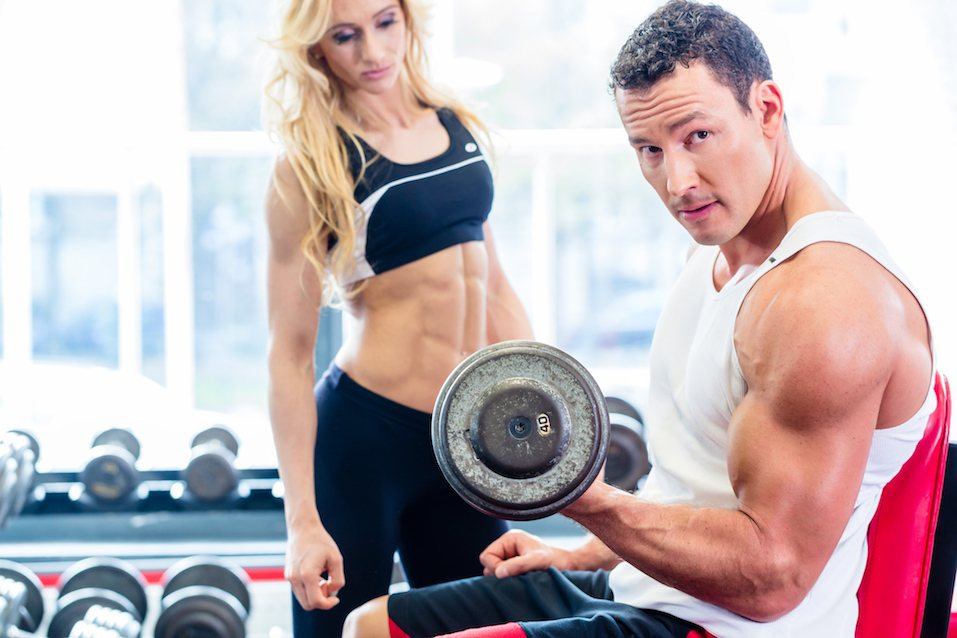Couple in fitness gym with dumbbells lifting weight as sport