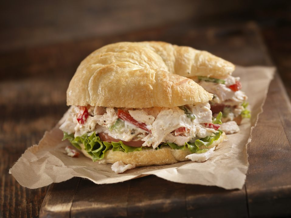 """A Creamy Chicken Salad Sandwich with Red Peppers, Cucumber, Lettuce and Tomato on a Croissant -"