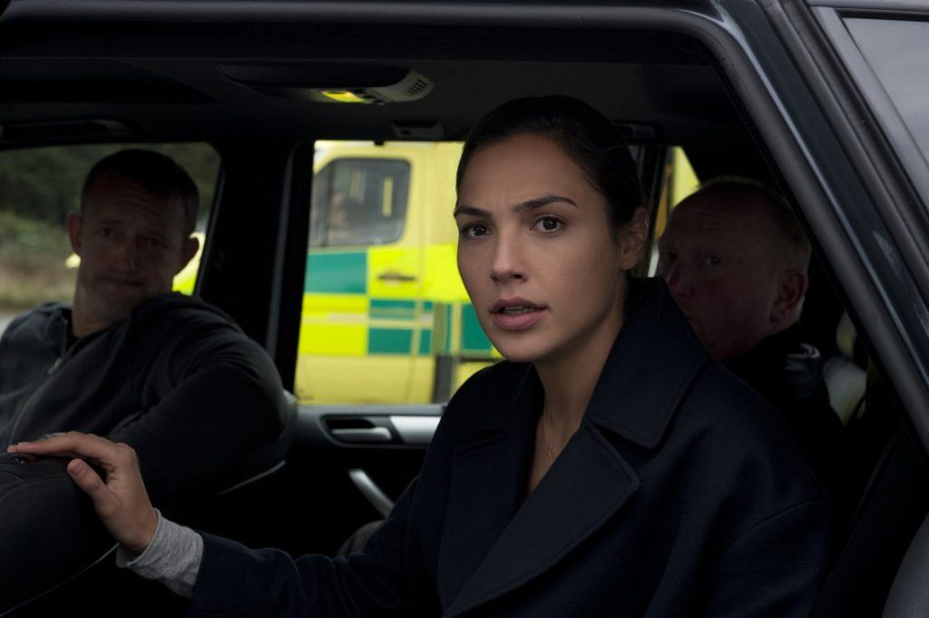Gal Gadot in a car with two men looking out the window