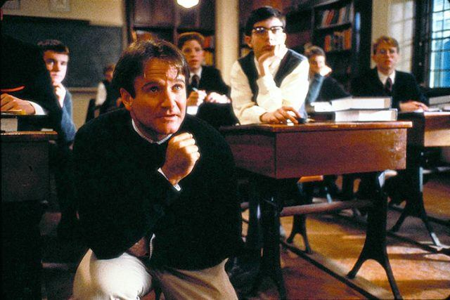 Robin Williams, crouched down in front of students sitting in a classroom