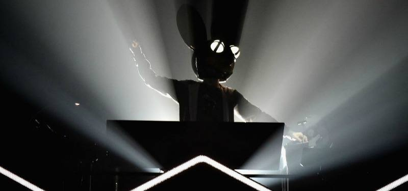 Deadmau5 is swinging his arms and is on a DJ booth.