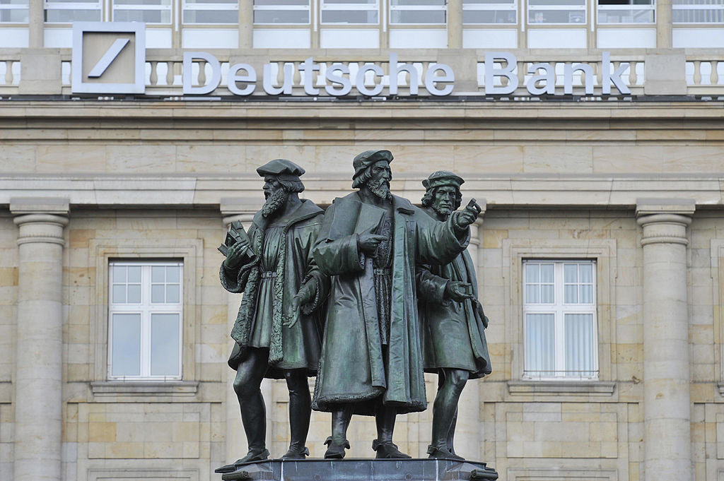 Statues forming the Gutenberg memorial stand in front of a Deutsche Bank building in Frankfurt