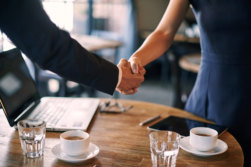 two people shake hands in cafe
