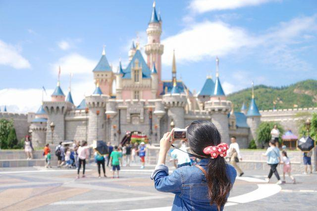 A woman taking a photo of the castle.
