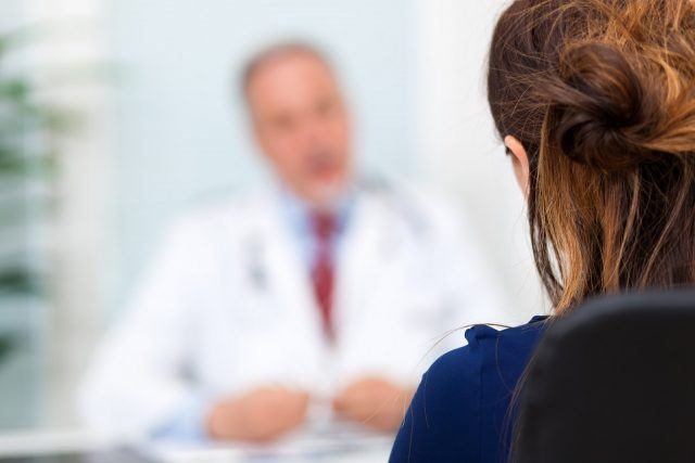 Doctor talking to a patient in an office.