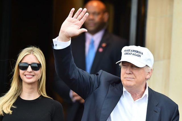 Donald Trump waves while standing next to Ivanka Trump.
