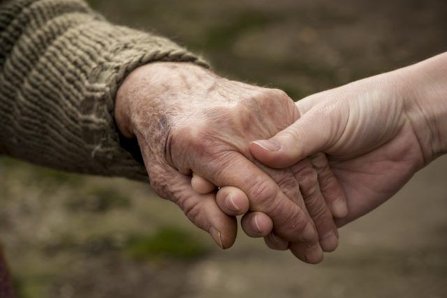 a young woman's hand holding an older person's hand