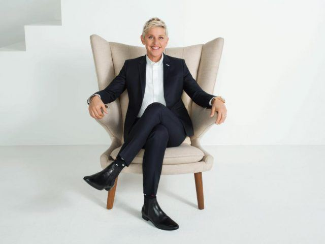Ellen DeGeneres sits on a white chair.