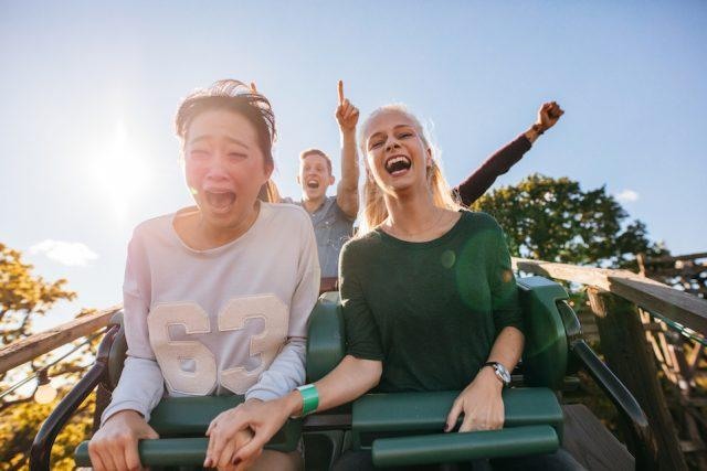 Enthusiastic young friends riding a roller coaster